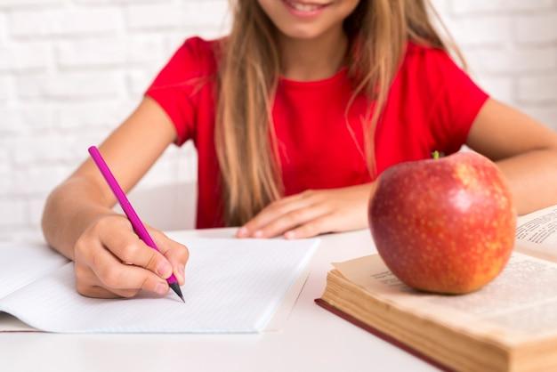 Ijverig schoolmeisje dat bij werkboek schrijft