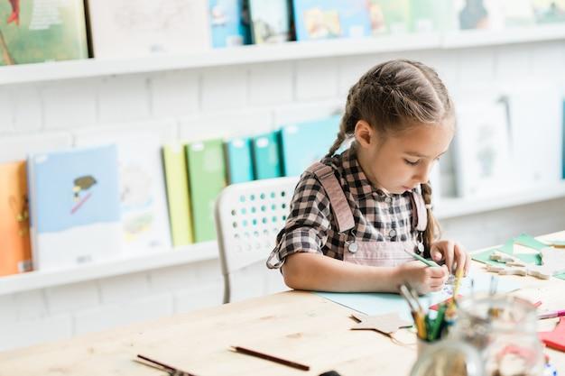 Ijverig schoolmeisje tekening kerst foto door bureau terwijl individueel werken aan les schilderen