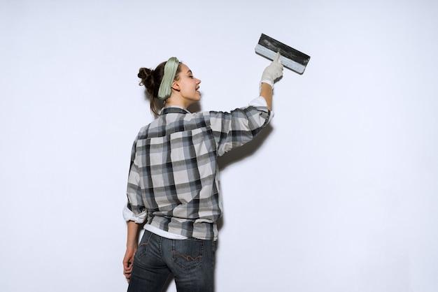 Ijverige jonge meisjesbouwer egaliseert de muren met een spatel