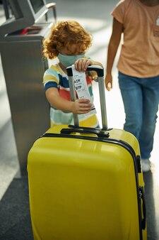 Ijverige jongen die een papieren sticker aan een gele koffer bevestigt
