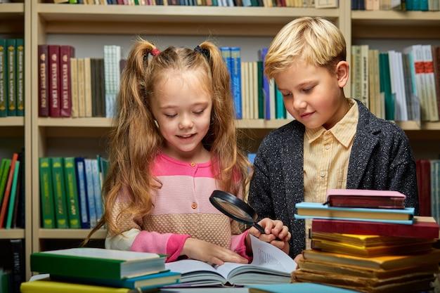 Ijverige leerling met boeken in bibliotheek, jongen en meisje gebruiken vergrootglas voor beter leren en lezen