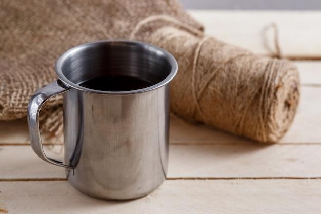 Ijzer uitstekende mok met thee op houten lijst. wirwar van draden