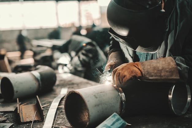 Ijzerarbeider in beschermend pak, masker en handschoenen die pijp lassen. werkplaats interieur.
