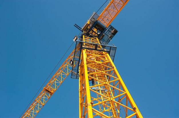 Ijzeren cabine van een gele kraan tegen een blauwe lucht