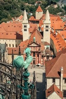Ijzeren haan beeldje bovenop de sint-vituskathedraal met uitzicht op de rode pannendaken van de stad in praag, tsjechië
