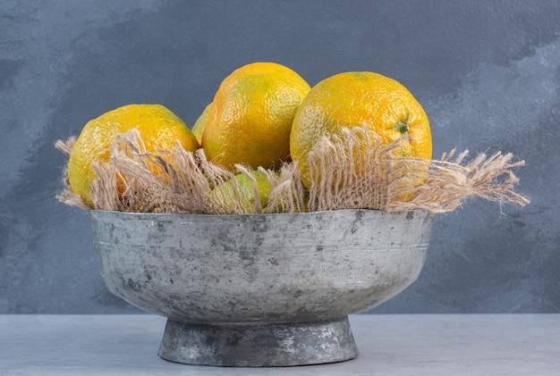 Ijzeren kom vol mandarijn op grijze achtergrond.