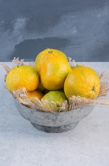 Ijzeren kom vol mandarijnen (sinaasappels, clementines, citrusvruchten) over grijze achtergrond.