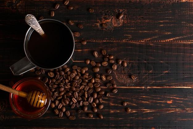 Ijzeren mok met zwarte koffie, honing en koffiebonen op een houten tafel. copyspace.