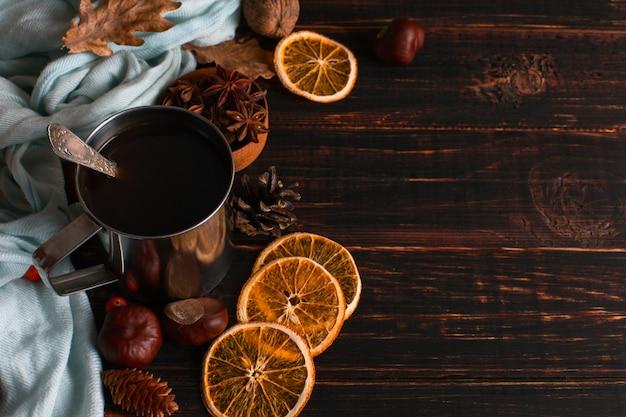 Ijzeren mok met zwarte koffie, kruiden, droge sinaasappelen, op een achtergrond van een sjaal, droge bladeren op een houten tafel. herfststemming, een warm drankje. copyspace.