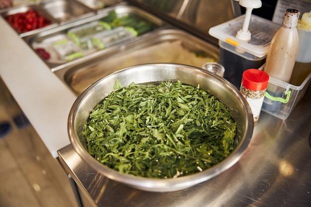 Ijzeren plaat met water en rucola na het schoonmaken voor het koken op tafel in café