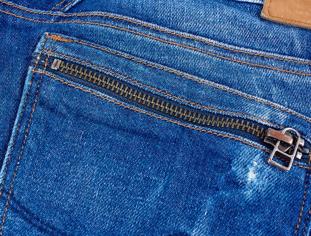 Ijzeren slang op de achterzak van een blauwe spijkerbroek, volledig frame