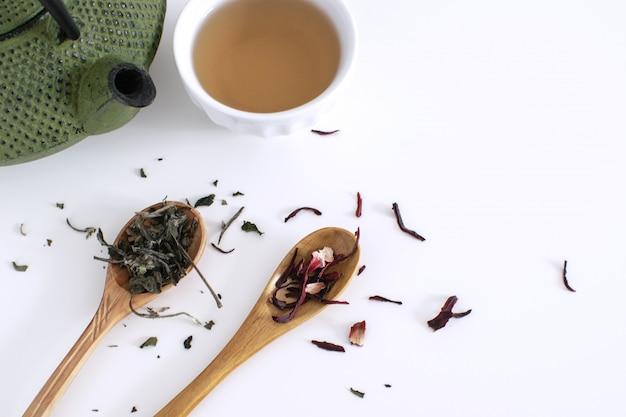 Ijzeren theepot koppen houten lepel theebladen gedroogde hibiscus witte achtergrond