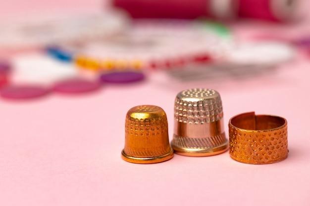 Ijzeren vingerhoedjes om op een roze ondergrond te naaien