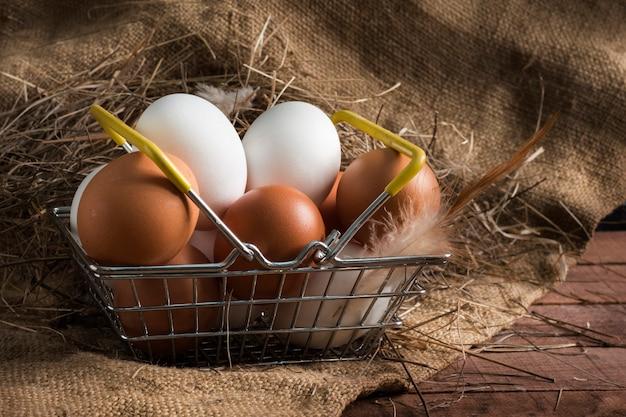 Ijzeren voedselmand met bruine en witte eieren op een bruine houten achtergrond met jute.