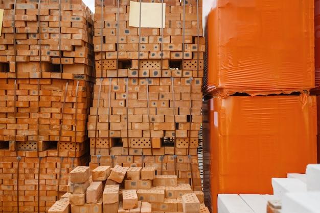 Ijzerwarenassortiment, pakken rode bakstenen buiten, niemand. keuze van bouwmaterialen en gereedschappen in de doe-het-zelfwinkel, rijen met producten