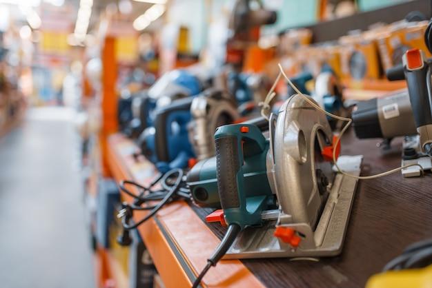 Ijzerwarenassortiment, plank met handcirkelzagen, niemand. keuze van elektrisch gereedschap in doe-het-zelfwinkel, rijen producten, elektrisch instrument