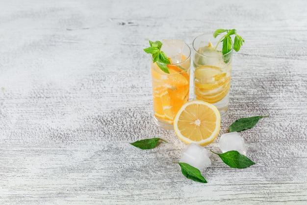 Ijzig detoxwater in glas met sinaasappel, citroen, munt hoge hoekmening over een grungeachtergrond