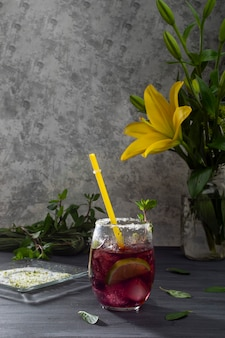 Ijzig drankje met ijs en schijfjes citroen op een grijze tafel en een vaas met gele bloemen