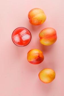 Ijzig sap in een glas met bovenaanzicht van nectarines op een roze oppervlak