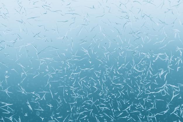 Ijzige kristallen op vensterglas. sfeervol mintblauw aqualicht van bevroren venster. azuurblauw ijzig patroonclose-up. gedetailleerde transparante aquamarijntextuur in macro met copyspace. fris weer.