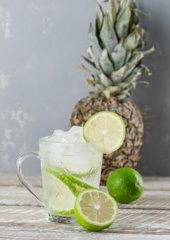 Ijzige mojito cocktail met limoenen, ananas in een kopje op houten en gips, zijaanzicht.