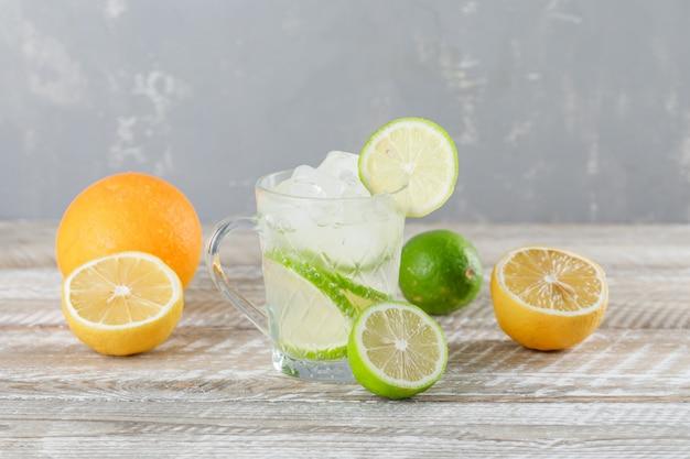 Ijzige mojitococktail in een kop met limoenen, sinaasappel, citroen zijaanzicht op houten en pleistermuur