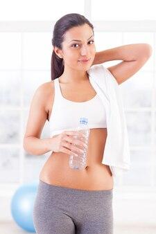 Ik ben altijd in goede vorm. aantrekkelijke jonge vrouw in sportkleding die een fles water vasthoudt en naar de camera kijkt terwijl ze in een sportclub staat