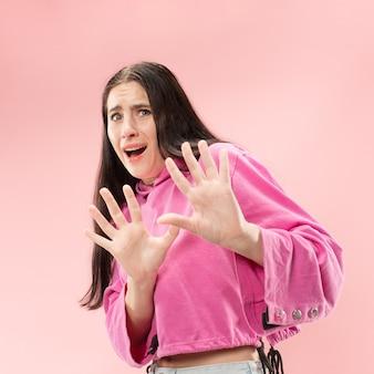 Ik ben bang. schrik. portret van de bange vrouw. zakenvrouw staande geïsoleerd op trendy roze ruimte