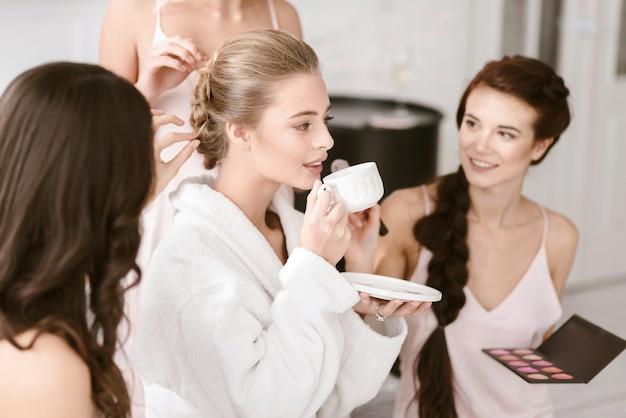 Ik ben binnenkort verloofd. nadenkende opgetogen jonge bruid die in de witgekleurde kamer zit terwijl ze zich klaarmaakt met de bruidsmeisjes en thee drinkt