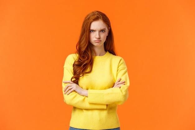 Ik ben boos. beledigd sulky schattig en verlegen roodharige krullend meisje, gekruiste armen borst, mokkend boos en gespannen, fronsende blik