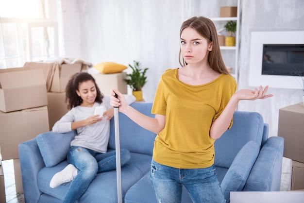 Ik ben boos. mooi jong meisje dat de vloer schoonmaakt en boos is op haar luie kamergenoot terwijl ze sms't op de bank in plaats van haar te helpen