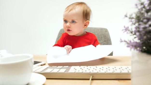 Ik ben de baas. kind babymeisje zit met toetsenbord van moderne computer of laptop in witte studio