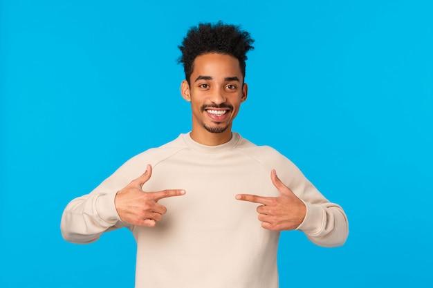 Ik ben degene. vrolijke en vriendelijke zelfverzekerde gelukkige gelukkige afro-amerikaanse man met hipster afro-kapsel, zichzelf wijzend, wil deelnemen, vrijwilliger, opscheppen of praten opschepperige persoonlijke prestatie