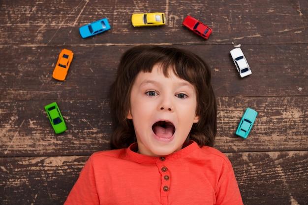 Ik ben dol op auto's. bovenaanzicht van een kleine jongen die op de grond ligt en naar de camera kijkt en glimlacht
