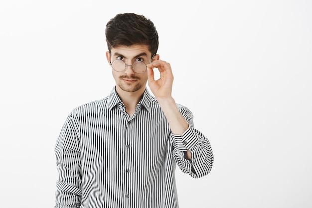 Ik ben geïntrigeerd. knappe zelfverzekerde jonge blanke mannelijke collega, kijkend van onder voorhoofd met opgetrokken wenkbrauw, rand van bril vasthoudend, wantrouwend en geïnteresseerd in gespreksonderwerp