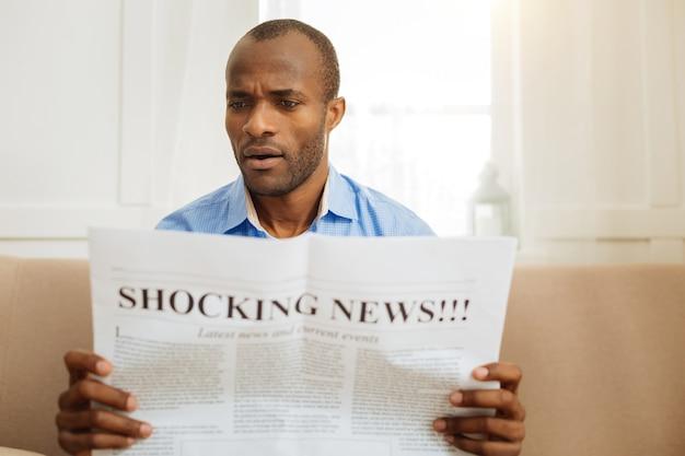 Ik ben geschokt. geconcentreerde verbaasde afro-amerikaanse man die een krant vasthoudt en leest terwijl hij op de bank zit