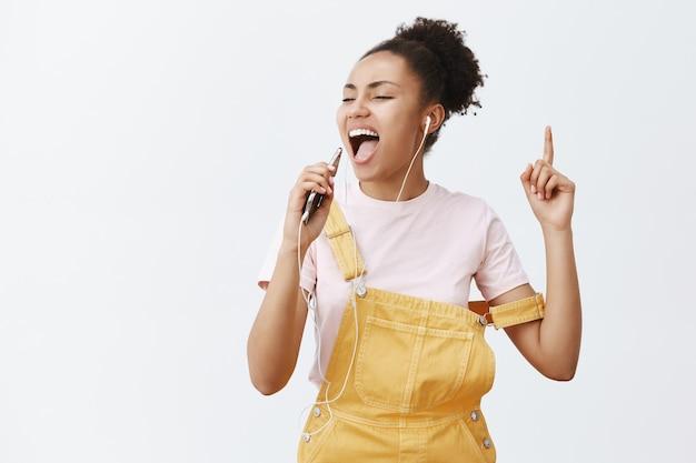 Ik ben het beste in karaoke. portret van zorgeloze opgewonden en aantrekkelijke vrouw met donkere huid in gele overall, muziek luisteren en meezingen in oortelefoons, microfoon maken van smartphone