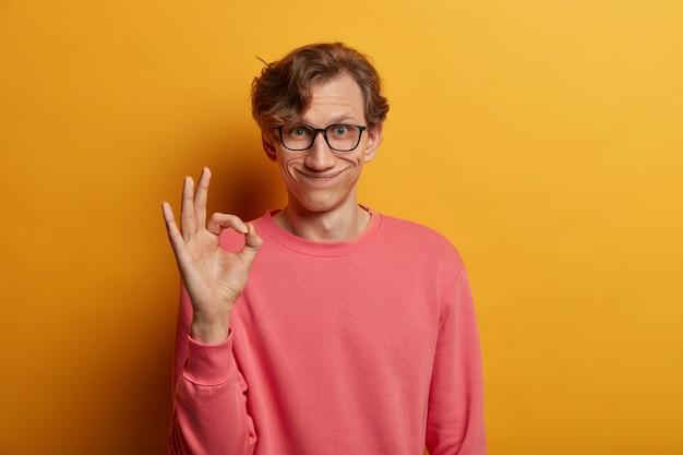Ik ben het eens met uw suggestie. glimlachende knappe man lacht aangenaam, maakt goed teken, spreekt goedkeuring uit, draagt bril en roze trui, heeft alles onder controle, geïsoleerd op gele muur
