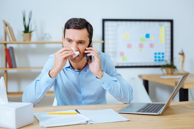 Ik ben het. pessimistisch donkerbruin mannetje dat aan het werk is en de neus afveegt terwijl hij de telefoon vasthoudt