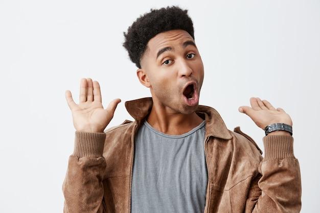 Ik ben hier weg. portret van jong grappig donkerhuidig afrikaans mannetje met krullend haar in grijs t-shirt onder bruine jas wordt geschokt hoorzitting provocerend nieuws over oude vriend.