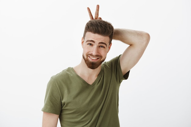 Ik ben je konijn, schat. portret van brutaal en schattig romantisch vriendje dat in een speelse bui ronddoolt en oren of overwinningsteken op hoofd toont en mooi glimlacht over witte muur