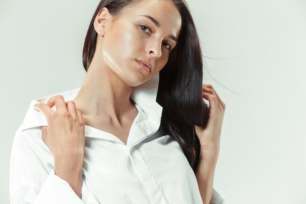 Ik ben jong en knap. portret van mooi donkerharig meisje op grijze studioachtergrond. mode blanke vrouw. portret van jonge mannequin. lang haar. bruine ogen
