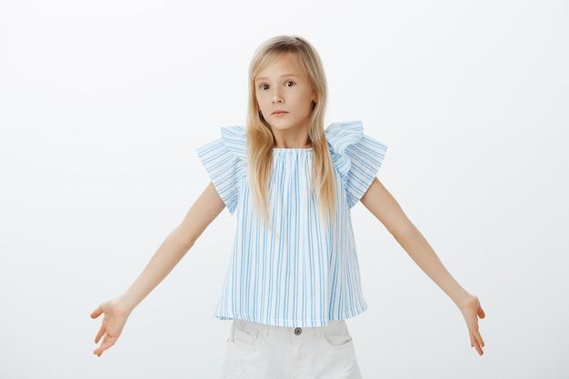 Ik ben maar een kind, wat weet ik. portret van clueless schattig meisje met blond haar, schouderophalend en spreidende handpalmen in onbewust gebaar, ondervraagd en verward over grijze muur