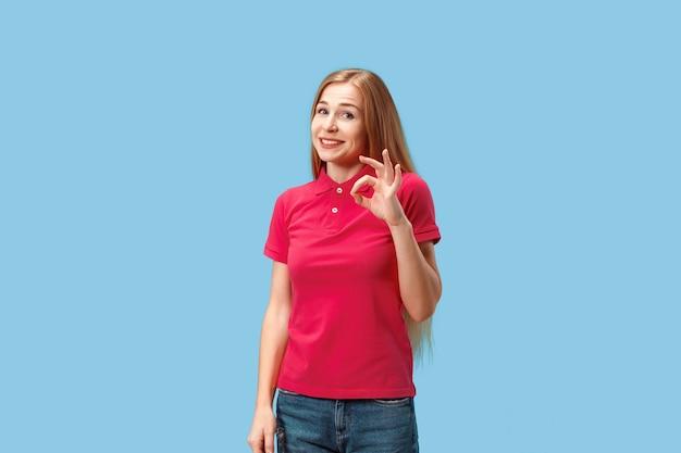 Ik ben ok. gelukkig zakenvrouw, teken ok, lachend, geïsoleerd op trendy blauwe studio achtergrond. mooi vrouwelijk portret van halve lengte. emotionele vrouw. menselijke emoties, gezichtsuitdrukking concept. voorkant