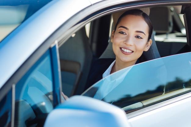 Ik ben onderweg. opgetogen vrolijke vrouw die haar auto bestuurt terwijl ze naar haar werk gaat