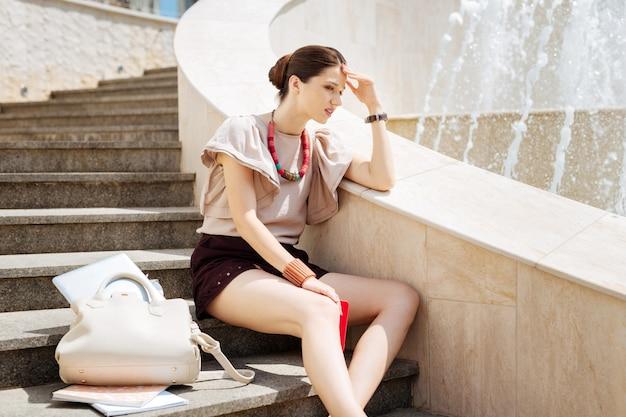 Ik ben ontslagen. triest jonge vrouw zittend op de trap terwijl ze aan haar werk denkt