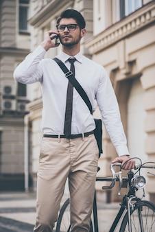 Ik ben over vijf minuten! zelfverzekerde jongeman met een bril die op een mobiele telefoon praat en zijn fiets vasthoudt terwijl hij buiten staat