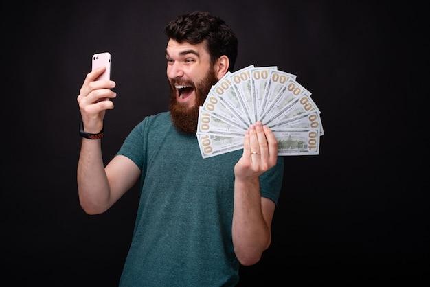 Ik ben rijk ! ik won! jonge, bebaarde verraste man die naar zijn telefoon kijkt en een hoop geld in zijn hand houdt
