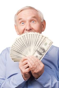 Ik ben rijk! portret van een gelukkige senior man die zijn mond bedekt met geld en naar de camera kijkt en terwijl hij tegen een witte achtergrond staat