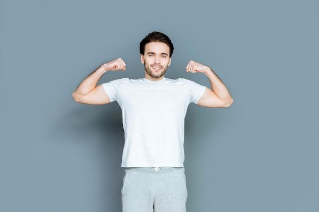 Ik ben sterk. vrolijke, goedgebouwde knappe man die lacht en naar je kijkt terwijl hij je zijn spieren laat zien